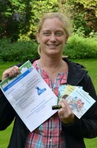 Projektkoordinatorin Birgit Heinekamp zeigt die Rätseltour für Kinder und Familien und die kleinen Belohnungen für Kinder. (Foto: B. Kalle – Kreis Unna)