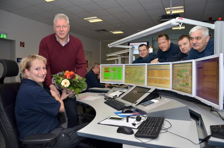Sachgebietsleiter Jürgen Wirth gratulierte Leitstellendisponentin Alexandra Zumdick und ihren Kollegen mit einem Blumenstrauß zur 100.000. Leitstellentätigkeit in diesem Jahr. (Foto: B. Kalle – Kreis Unna)