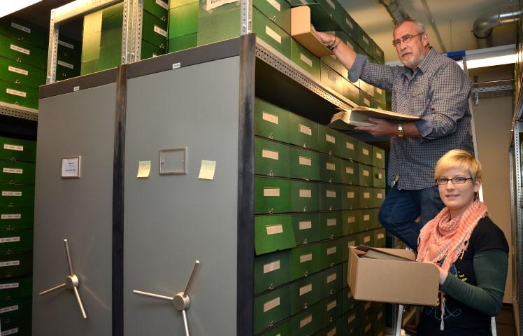 Archivar Josef Börste und Jessica Hohmann sortieren Dokumente im neuen Rollregallager des Kreisarchivs. (Foto: B. Kalle – Kreis Unna)
