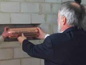 Geschäftsführer Joachim Kahle versenkt die Dokumentenrolle mit den Bauplänen samt Duickstein-Etikett. (Foto: WFG Kreis Unna)