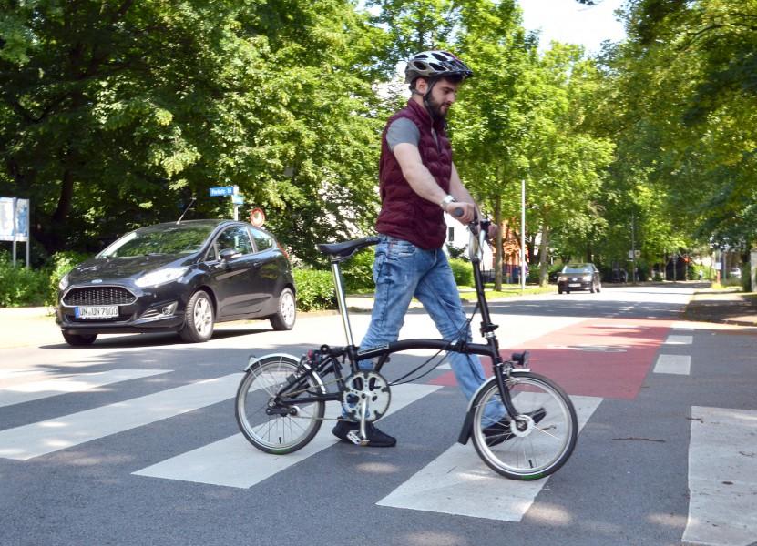 So ist es richtig: Kreis-Auszubildender Ömer Temur schiebt sein Fahrrad über den Zebrastreifen. (Foto: B. Kalle – Kreis Unna)