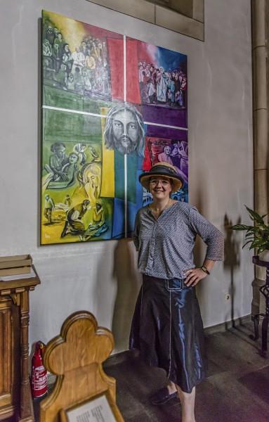 Ilka Breker vor ihrem Gemälde, das das farbige Symbolkreuz des Zukunftsbildes aufgreift.jetzt hgofft die Künstlerin auf die Mitrarbveiter der Gemeindemitglieder an ihrem neuen Buchprojekt. (Foto: P. Gräber)