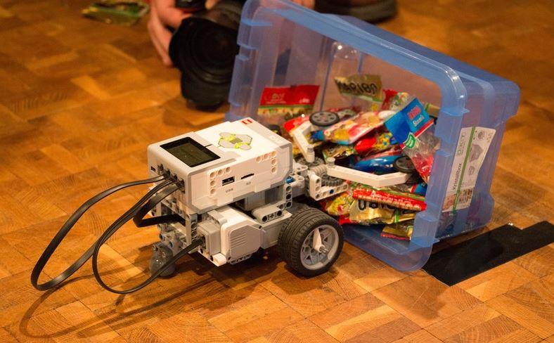 Ein von Schülern des vorigen Lehrganges programmierter Roboter versucht, Gummibärchen aus einer Kiste zu greifen. (Foto: WFG)