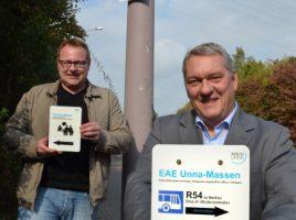 Fachbereichsleiter Ferdinand Adam (r.) und Sebastian Schmidt aus der Erstaufnahmeeinrichtung in Unna-Massen zeigen die neuen Schilder. (Foto: B. Kalle – Kreis Unna)