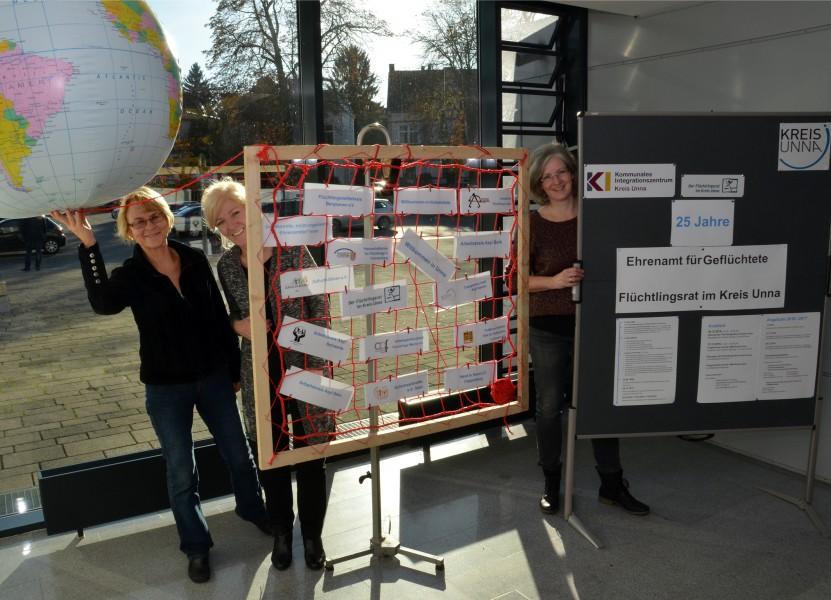 Anne Nikbin, Ina Ravenschlag und Nicola Schneider (von links) aus dem Kommunalen Integrationszentrum Kreis Unna (KI) zeigen die Ausstellung. Foto: Birgit Kalle – Kreis Unna