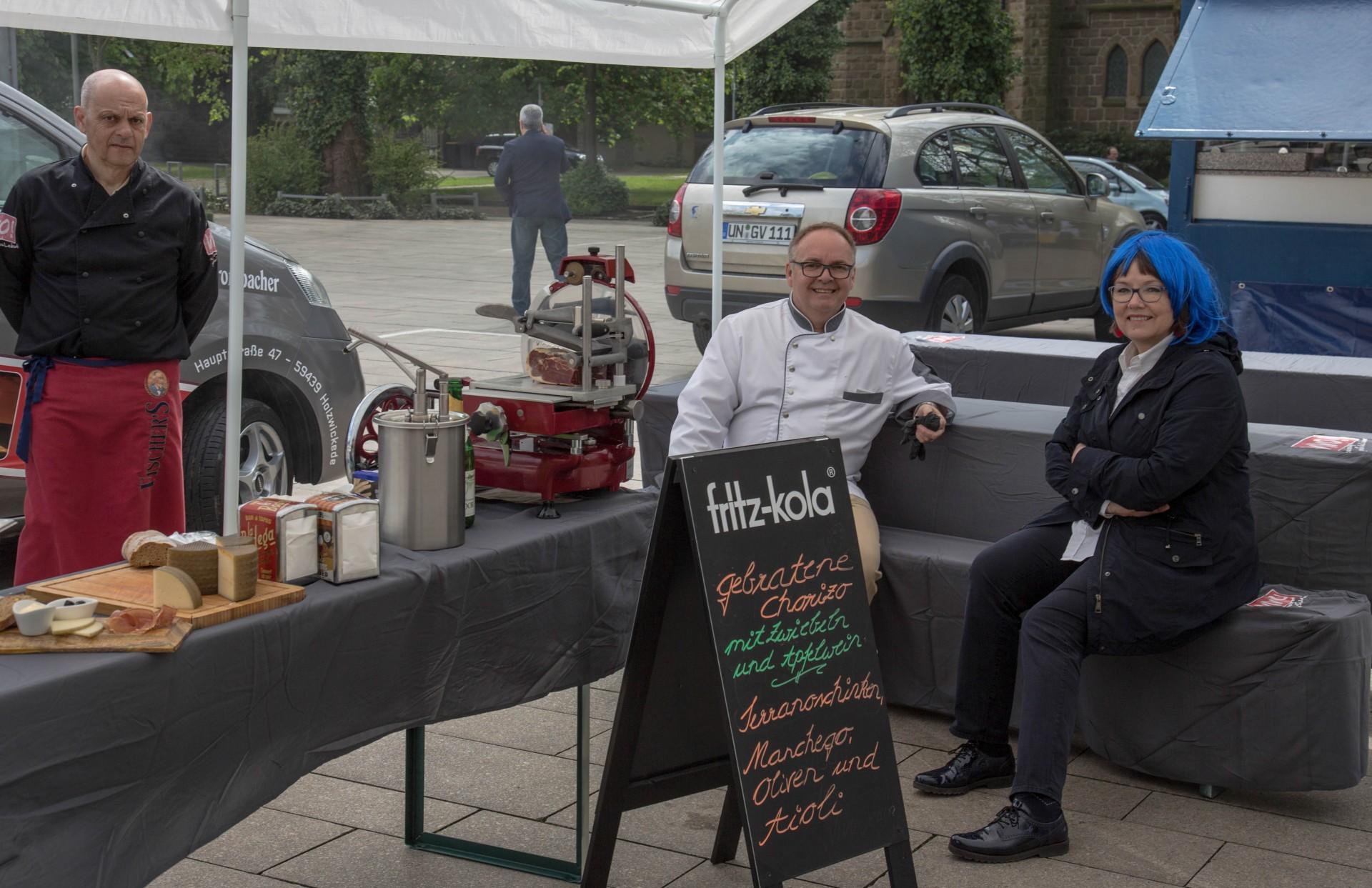 Französisch-spanische Gespräche: Freundeskreis-Geschäftsführerin Ute Hake (ebenfalls mit blauer Perücke) am Stand von Vivo-Gastronom Jens Reckermann (M.). (Foto: P. Gräber - Emscherblog.de)