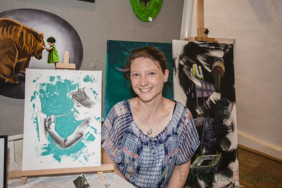 """Die junge Malerin Tatjana Kugel aus Opherdicke, hier neben einem Selbstportrait, hatte sozusagen ein """"Heimspiel"""" beim Malermarkt. Die Bilder der Opherdickerin sind teils gespachtelt, teils in Airbrush-Technik gemalt. (Foto: P. Gräber - Emscherblog.de)"""