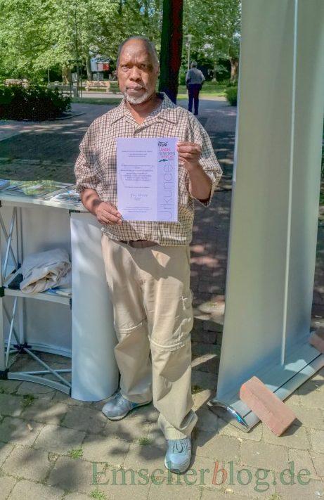 John Corcas Okellos mit der Urkunde, die der Seniorenbeirat von der Landes-Seniorenvertretung für seine ehrenamtliche Arbeit erhielt. Foto: P. Gräber Emscherblog.de)
