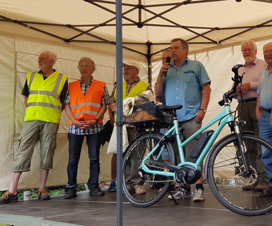 Auf der Bühne des Gemeindefestes in Holzwickede stellt Volker Rotthauwe das Kirchenrad vor. (Foto: privat)