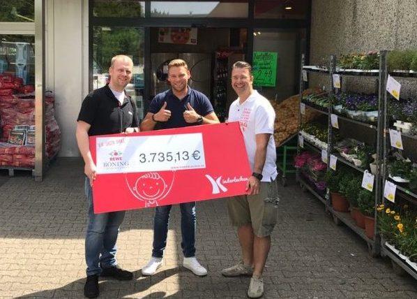 Markt-Inhaber Florian Böning (l.) und Christian Barnick (Mitte), Rewe Dortmund, übergaben den symbolischen Spendenscheck in Höhe von rund 3.735 Euro an Kinderlachen-Mitgründer Marc Peine. Foto: Kinderlachen)