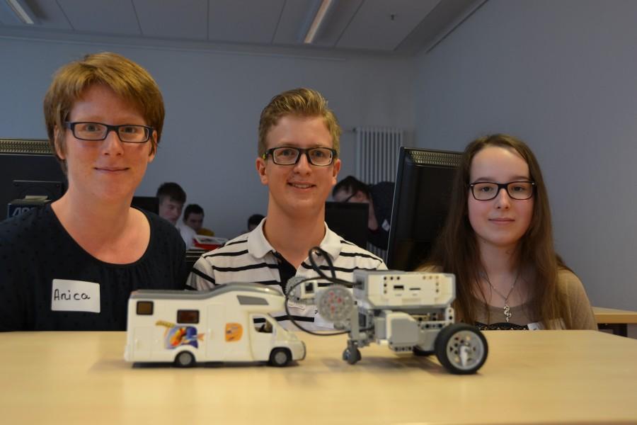 : Jannis Lichtner hatten den Roboter so programmiert, dass dieser ein Spielzeug-Wohnmobil abschleppte. Anica Althoff (links) und Samira Bergau überzeugten sich vom Ergebnis. (Foto: WFG - Ute Heinze)