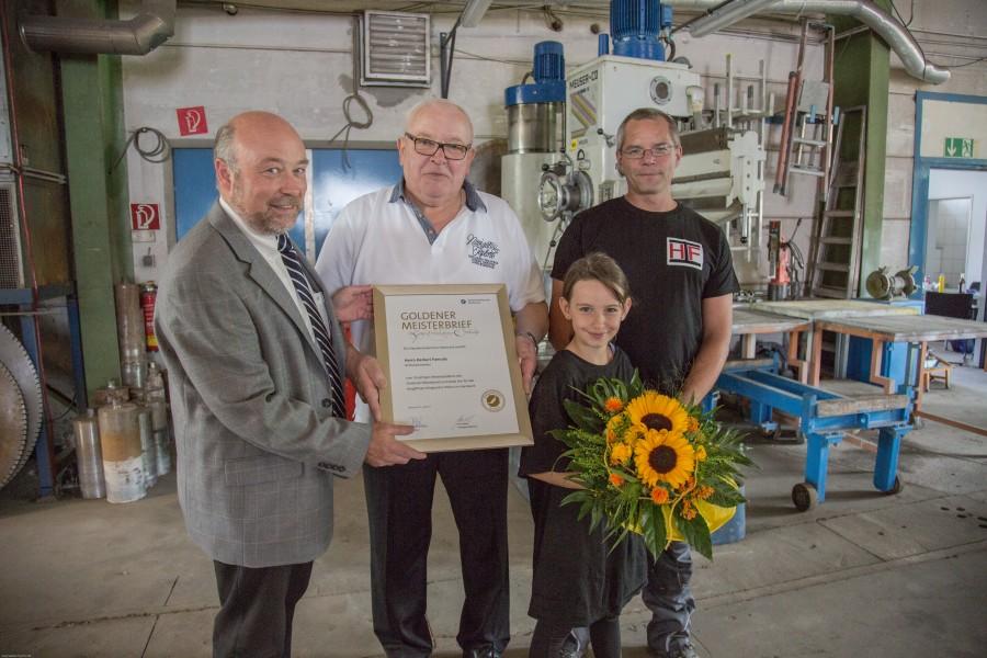 Von links: Innungs-Obermeister Christoph Knepper überreicht Herbert Famulla, hier mit seinem Sohn Björn und Enkelin Lucy, den Goldenen Meisterbrief. (Foto: P. Gräber - Emscherblog.de)