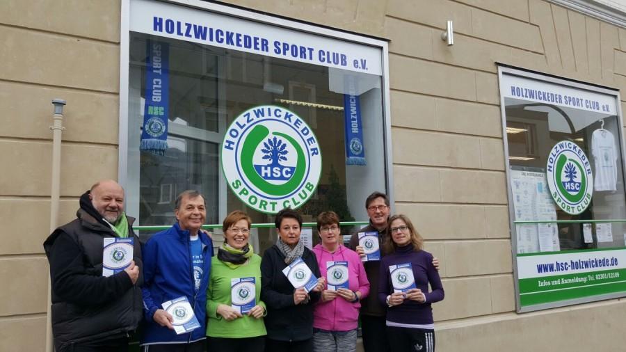 Vor dem Ladenlokal der HSC-Gesundheitssportabteilung an der Hauptstraße präsentieren HSC-Ehrenvorsitzender Rolf Unnerstall, Übungsleiterinnen und -leiter das neue Halbjahres-Programm. (Foto: HSC)