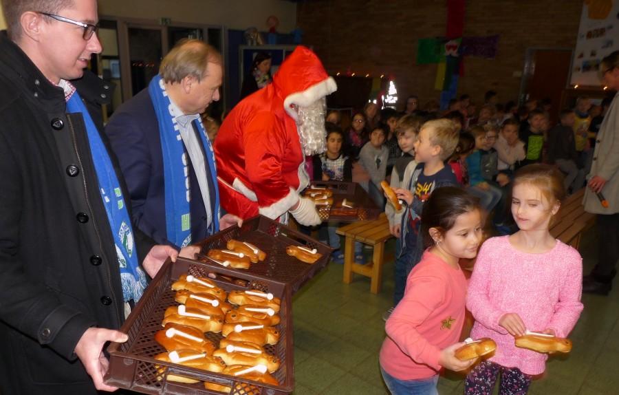 Alle Hände voll zu tun hatten (von links) Sebastian Benett und Udo Speer vom HSC-Vorstand, um den Nikolaus beim Verteilen der Stutenkerle in der Aloysiusschule zu unterstützen. (Foto: privat)