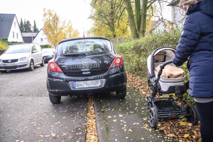 Eine Frau mit einem Kinderwagen kommt nicht am parkenden Auto vorbei. Muss sie mit Kind auf die Straße ausweichen, kann das gefährlich werden. Foto: Max Rolke - Kreis Unna