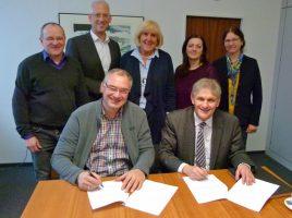 Landrat Michael Makiolla (vorne rechts) und Ralf Plogmann unterschrieben die Vereinbarung ebenso wie Rainer Klein (l.), Angelika Schindler (r.) und Sabina Cosentino (2.v.r.). Mit dabei waren auch Sozialdezernent Torsten Göpfert und Ausschussvorsitzende Angelika Chur. (Foto: Max Rolke - Kreis Unna)