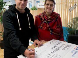 Daniel Krahn von Urlaubsguru und Birgit Poller von Wir für Holzwickede bei der Unterschrift. – Foto: Rienhoff/UNIQ GmbH