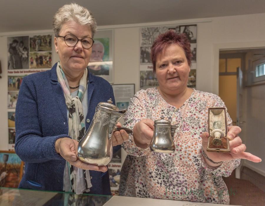 Monika Blennemann (l.) und Brigitte Skupch mit den drei Objekten, die der Historische Verein für die Heimatstube erworben hat: zwei silberene Kaffeekannen und ein Petschaft. (Foto: P. Gräber - Emscherblog.de)