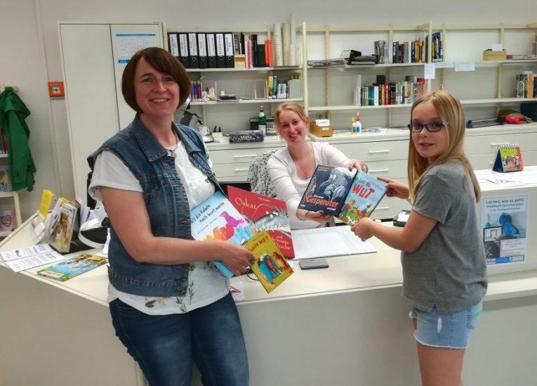 Claudia Sommer (.) und Johanna Häusler (r.) überreichten Silke Becker die fünf gespendeten neuen Bücher für das Bilderbuchkino. (Foto: privat)