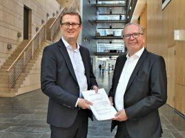 Bundestagsabgeordneter Oliver Kaczmarek übergibt die Unterschriftenliste an Dr. Rainer Wend ,den Leiter des Zentralbereiches Politik und Regulierungsmanagement der Deutschen Post DHL,. (Foto: SPD Unna )