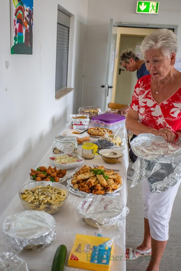 Ursula Voswinkel, Organisatorin des Festes, und Bürgermeisterin Ulrike Drossel (hinten), eröffnen das Buffet mit den landestypischen Spezialitäten. (Foto: P. Gräber - Emscherblog.de)