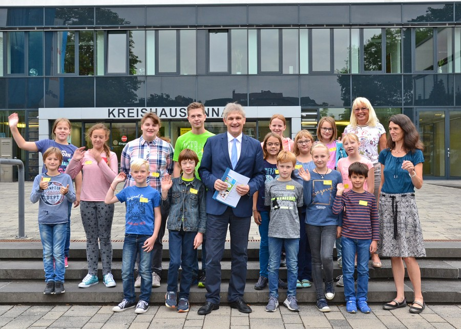 Landrat Michael Makiolla (vorne M.) begrüßte die Kinder gemeinsam mit Kinder-Uni-Organisatorin Martina Bier (hinten re.) und Sabine Leiße (Leiterin Planung und Mobilität, re.) im Kreishaus, bevor es auf die Fahrt nach Dortmund ging. (Foto: Max Rolke – Kreis Unna)