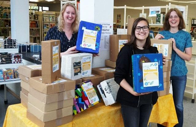 Bibliotheksmitarbeiterin Silke Becker, Praktikantin Jana Purr und Bibliotheksleiterin Kristina Truß (v.l.) mit den Überraschungskisten. (Foto: Norbert Spoor)