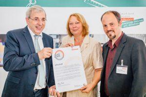 Klaus Kaiser (links) überreichte die Urkunde an Anita Flacke und Matthias Müller von der WFG. (Foto zdi.NRW Dominik Asbach)