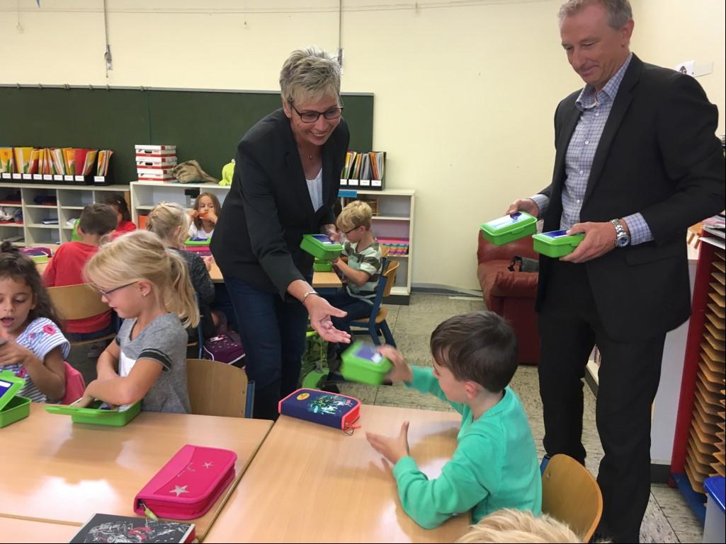 Bürgermeisterin Ulrike Drossel und Dirk Wißel, Kommunalbetreuer bei Innogy, verteilten heute Frühstücksboxen an die Schulanfänger der Nordschule. (Foto: Gemeinde holzwickede)