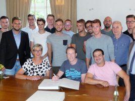 Holzwickedes Bürgermeister Ulrike Drossel (hier vorn mit HSC-Chefcoach Axel Schmeing) begrüßte heute die Meistermannschaft des HSC im Rathaus. Die Spieler trugen sich anschließend ins Goldene Buch der Gemeinde ein. (Foto: privat)