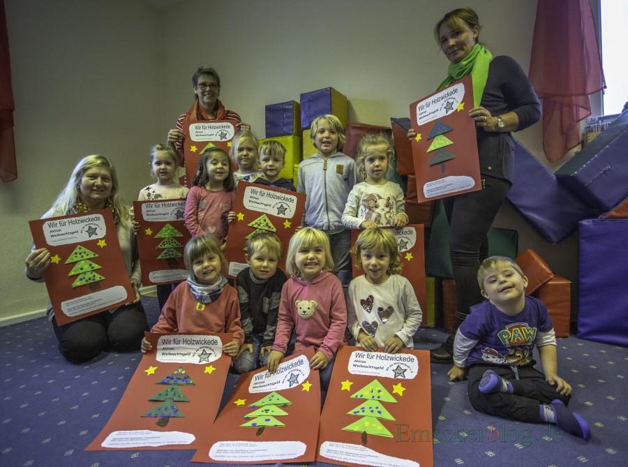 Die Kinder der evangelischen Kita Schatzkiste in Hengsen haben die Plakate für die Aktion Weihnachtsgeld in diesem Jahr gestaltet und heute an Andrea Rumpel (li.) und Birgit Poller (2.v.li.) vom Verein Wir für Holzwickede übergeben. (Foto: P. Gräber - Emscherblog.de)