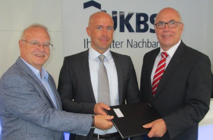 Aufsichtsratsvorsitzender Theodor Rieke (links im Bild) und Geschäftsführer Matthias Fischer (rechts) gratulierten dem neuen Prokuristen Alexander Krawczyk und wünschten einen guten Start ins neue Aufgabengebiet. (Foto: UKBS)