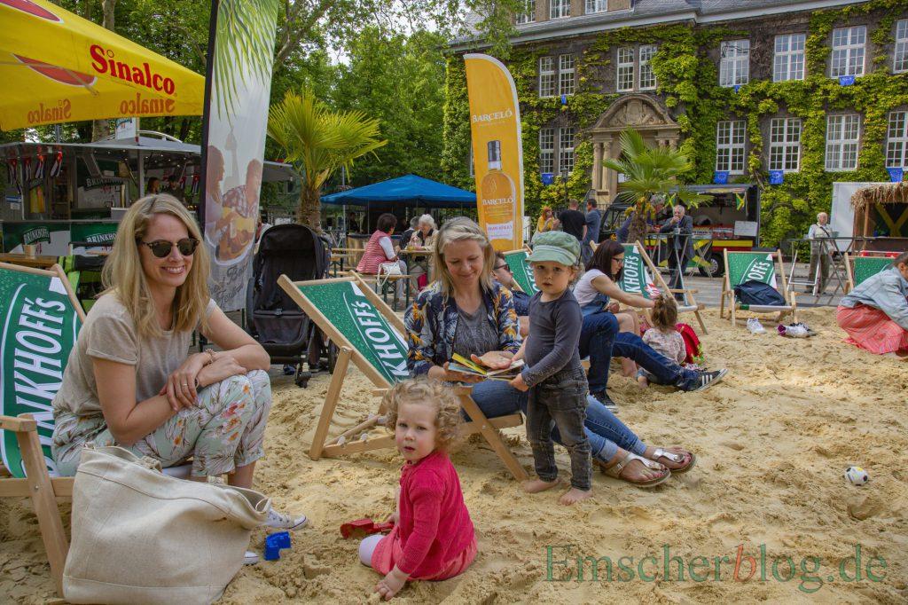 Da kommt Urlaubsfeeling auf: Auch Mia (vorne li.) und Titus (re.) mit ihren Müttern haben den großen Sandkasten vor dem Rathaus zur Eröffnung heute schon ausprobiert. (Foto: P. Gräber - Emscherblog)