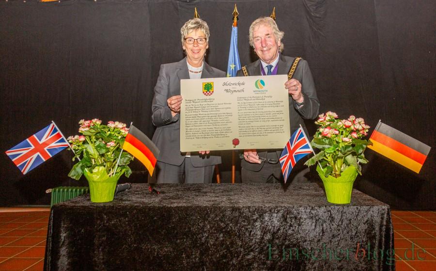 Bürgermeisterin Ulrike Drossel und der Councillor Graham Winter zeigen die unterschriebene Urkunde, mit der Holzwickede und Weymouth heute ihre Freundschaft erneuert haben. (Foto: P. Gräber - Emscherblog.de)