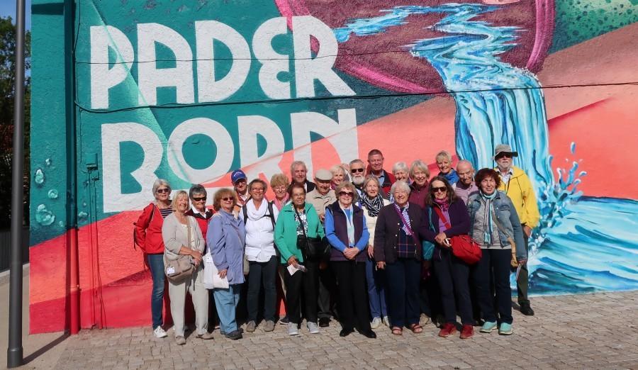 Das Foto zeigt die deutsche-englische Reisegruppe in Paderborn vor einer bunt bemalten Hausfassade. (Foto: privat)