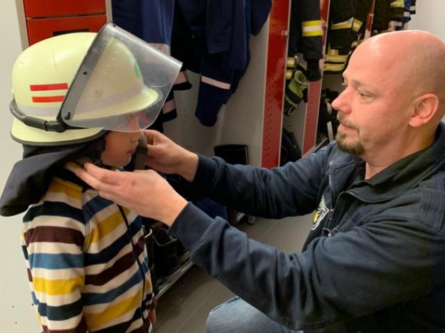 Um Julian (5 J.) zu trösten und abzulenken, zeigte Zugführer Jan Stappert dem Jungen die Ausrüstung der Feuerwehr... (Foto: privat)