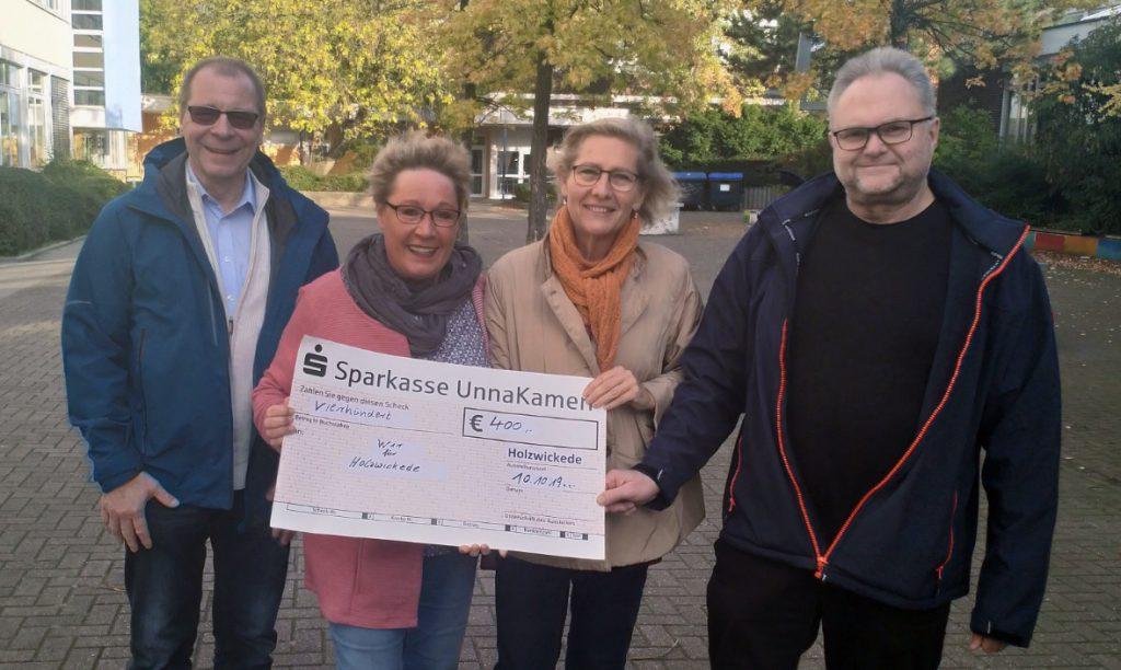 """Andrea Rumpel (2.v.l.) vom Verein """"Wir für Holzwickede"""" nahm den symbolischen Spendenscheck des Bürgerblocks dankend entgegen von Wolfgang Nowak, Barbara Schriek und Jörg Düllmann (r.) (Foto: P. Gräber - Emscherblog.de)"""