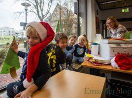 Die Kinder des Familienzentrums Löwenzahn mit den beiden erzieherinnen Gabi Frank (li.) und Franziska Herrmann (r.) beim Scjhmücken des Fensters im Bürgerbüro. (Foto: P. Gräber - Emscherblog.de)