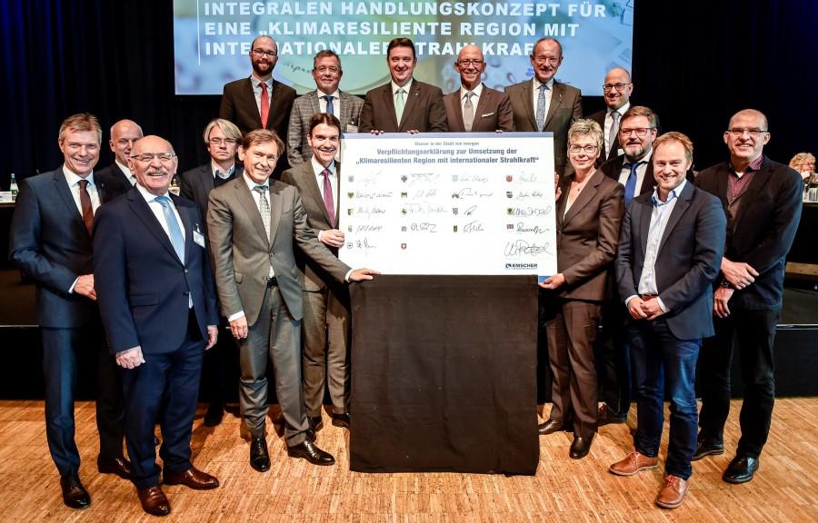 Die Vertreter der 16 Kommunen, unter ihnen Holzwickedes Bürgermeisterin Ulrike Drossel,  sowie  Prof. Dr. Uli Paetzel, Vorstandsvorsitzender der Emschergenossenschaft, stellten sich nach der Unterzeichnung der Verpflichtubgserklärung zum Gruppenbild. (Foto: Kirsten Neumann/EGLV)