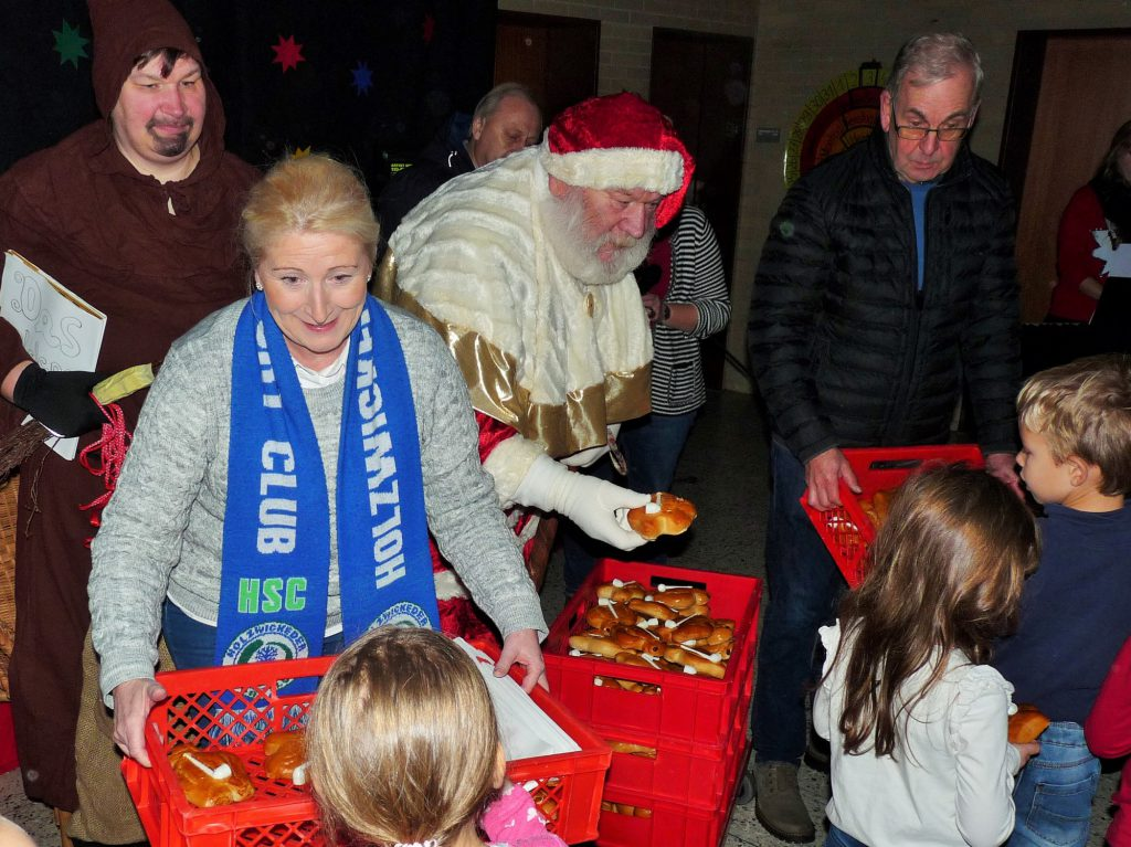 Dicht umdrängt waren Nikolaus, Knecht Rupprecht und der HSC-Vorstand, als sie gestern wie seit Jahren zum Nikolaustag Stutenkerle unter anderem an die Mädchen und Jungen der Aloysiusschule überreichten. (Foto: privat)