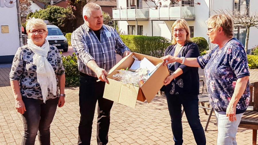 Barbara Schriek (v.r.) und Steffi Meier überreichen die Ostergrüße der Kinder an den Leiter des Perthes-Hauses, Bernhard Pendzialek und seine Kollegin Irina Nazarenus. (Foto: privat)
