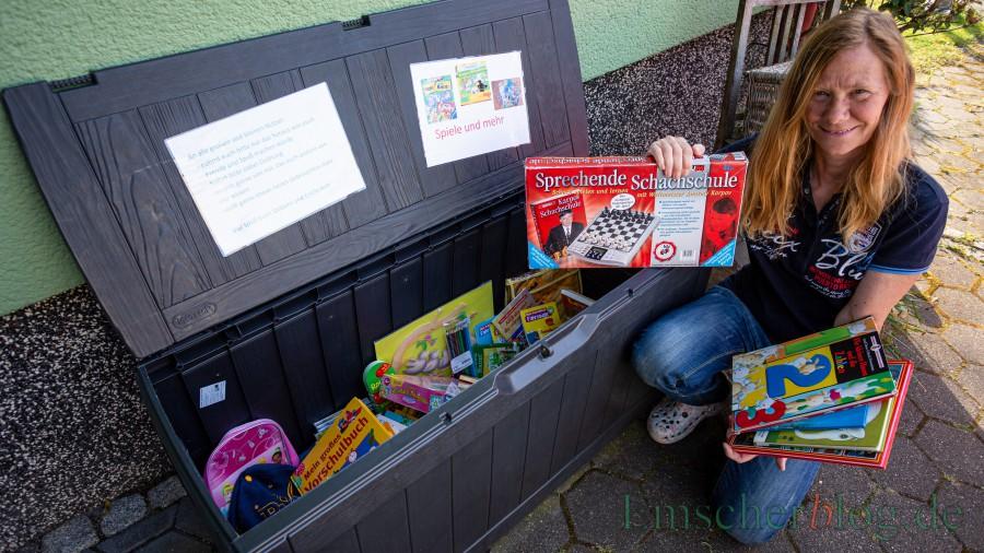 Ulrike Dürholt mit der Spiele- und Bücherkiste für Kinder: Die Box gegen die Langeweile steht vor ihrem Haus in der Melchiorstraße 4 und alle Kinder können sich daraus kostenlos bedienen. (Foto: P. Gräber - Emscherblog)
