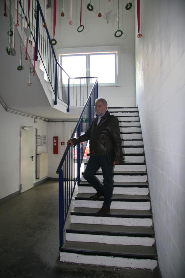Die aktuelle Treppensituation im Qualifizierungszentrum, die Barriere für Menschen mit Behinderungen ist: Werkstatt-Geschäftsführer Herbert Dörmann auf der Treppe. (Foto: Mobilitat.de)