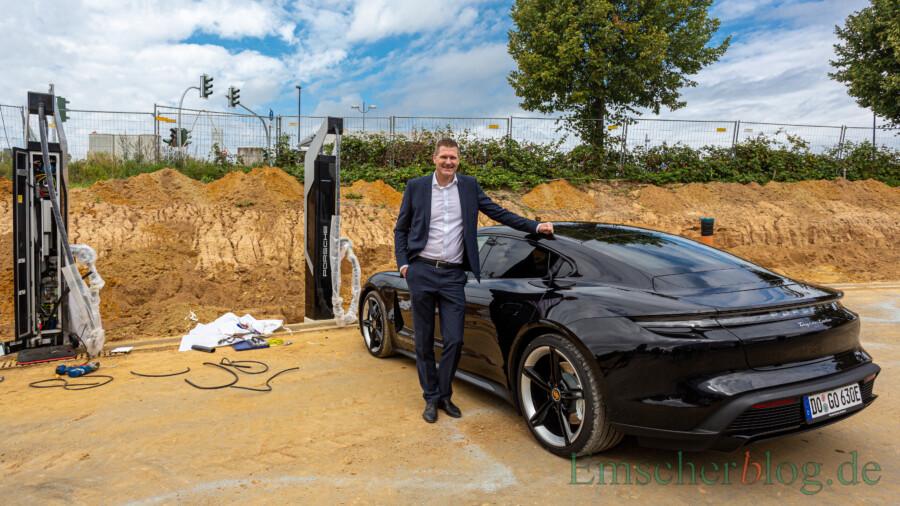 Christoph Kösters mit dem aktuelle Hoffnungsträger Porsches im E-Bereich, dem Taycan. Im Bild links zwei der Schnellladesäulen. (Foto: P. Gräber - Emscherblog)