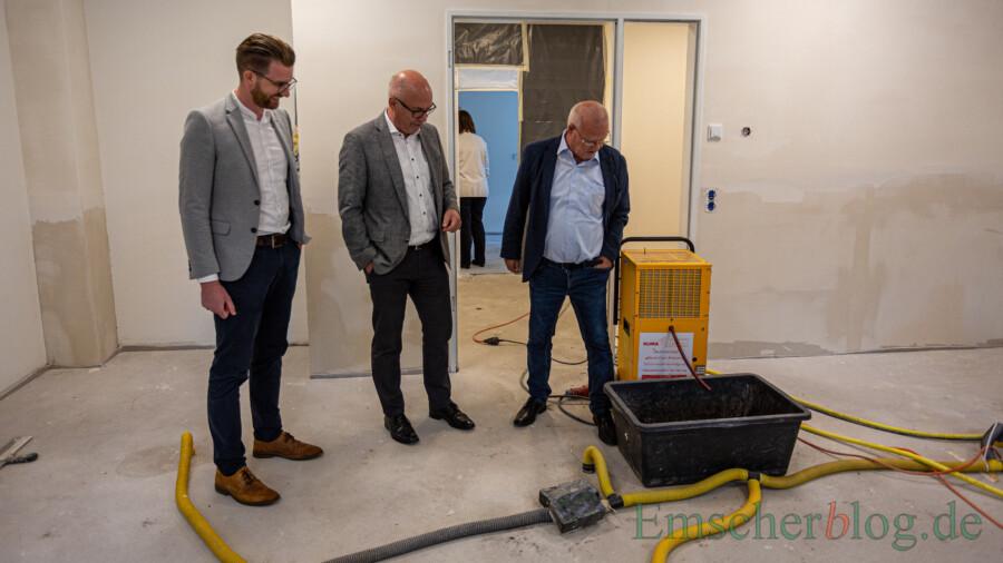 Vandalen haben einen Wasserschaden im Erdgeschiss verursacht: Simon Könemann, Matthias Fischer und Theo Rieke (v.l.) neben einem der großen Raumentfeuchtungsgeräte. (Foto: P. Gräber - Emscherblog)