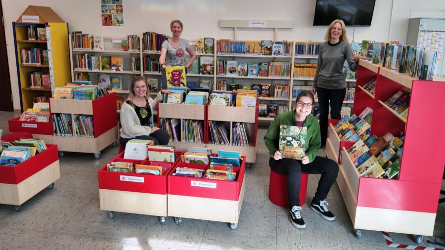 Lia Schulz (li.) und Mascha Wöstmann (2.v.r.) helfen den beiden Bibliotheksmitarbeiterinnen Silke Becker (2.v.l.) und Kristina Truß bei der Umgestaltung der Gemeindebücherei. (Foto: Gemeinde Holzwickede)