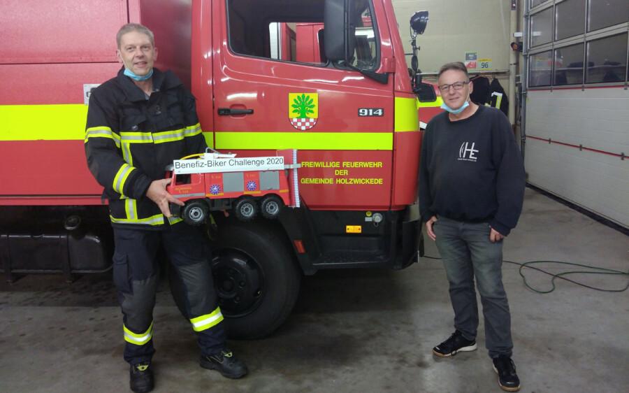 Der stellvertretende Leiter der Holzwickeder Feuerwehr und Leiter des Löschzuges 1, Peter Höttemann, nimmt das XXL-Modell des Feuerwehrautos  aus den Händen von Vereinsbotschafter Frank Brockbals entgegen, um es an die Kameraden der Feuerwehr Dortmund weiterzureichen. (Foto: privat)
