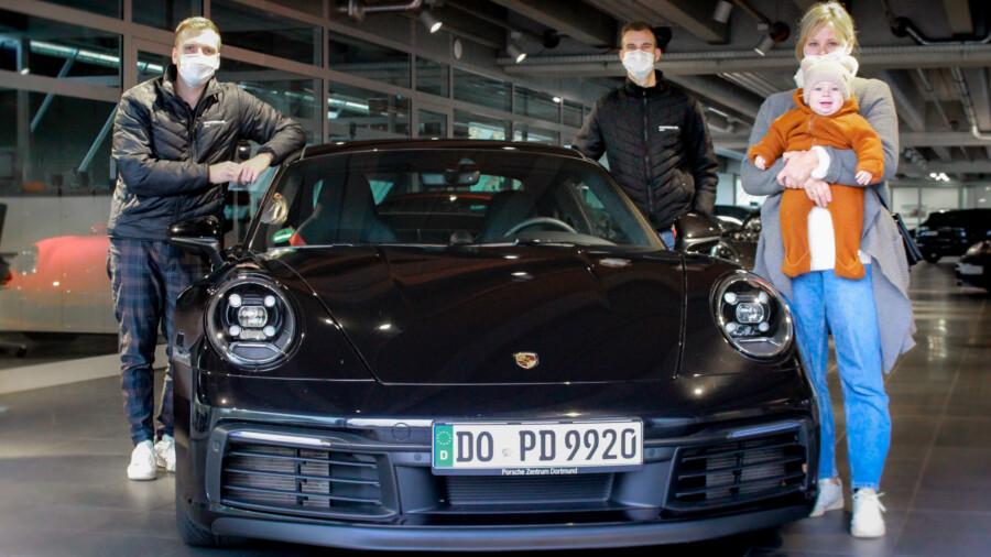 Übergabe eines Fahrzeuges an eine Kundin im Porsche-Zentrum Holzwickede durch die Mitarbeiter Robin Walther (li.) und Nils Feddersen. (Foto: Porsche Zentrum Dortmund)