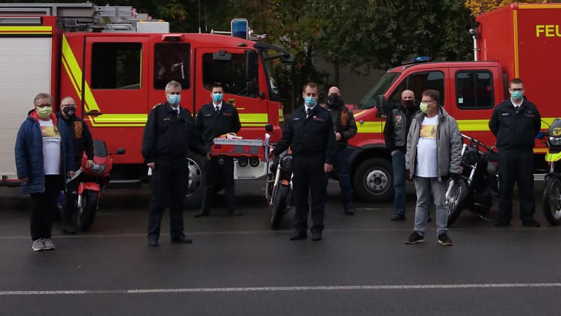 Jens Preetz (5.v.r.) überreicht das XXL-Feuerwehrauto an Oliver Nestler von der Dortmunder Berufsfeuerwehr. Im Bild ganz links: Annemarie Hunecke, die Vorsitzende des Vereins Auszeit für die Seele. (Foto: privat)
