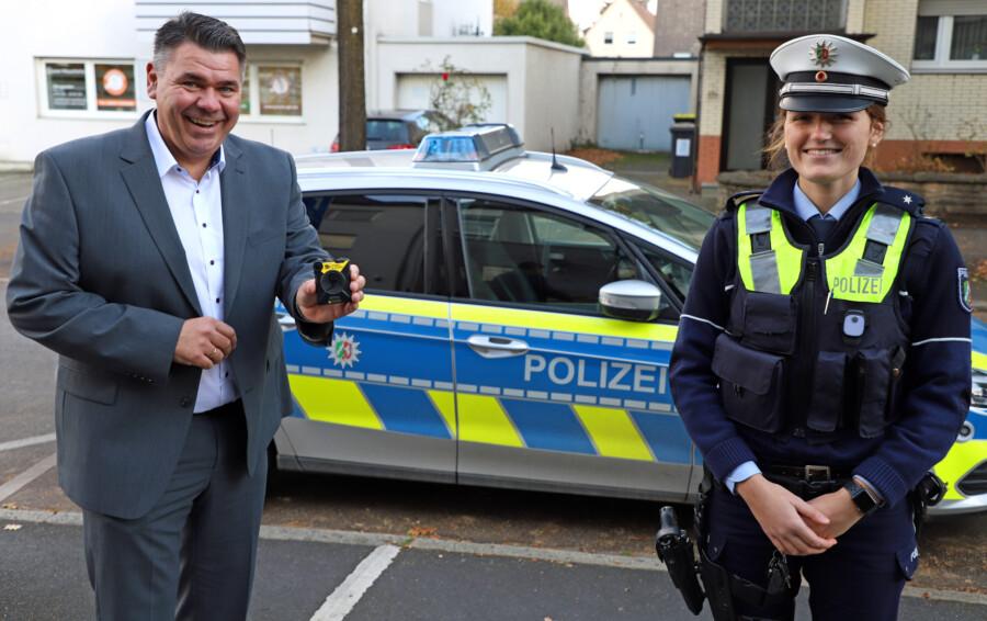 Landrat Mario Löhr, Leiter der Kreispolizeibehörde Unna, und eine Polizeibeamtin stellen eine der Bodycams vor, dien euerdings  von der Polizei im Kreis Unna bei kritischen Einsatzlagen eingesetzt wird.  (Foto: Kreispolizeibehörde Unna)
